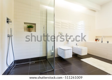 Tiled bathroom interior with the toilet and urinal in rectangular shape and glazed, minimalistic shower
