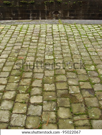 tiled cobble stone pavement with moss near the harbor - stock photo