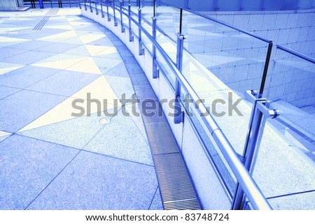 tiled floor, metallic handrails and glass fence fragments of modern urban square
