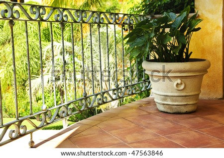 Tiled Mexican balcony with potted plant near railing - stock photo