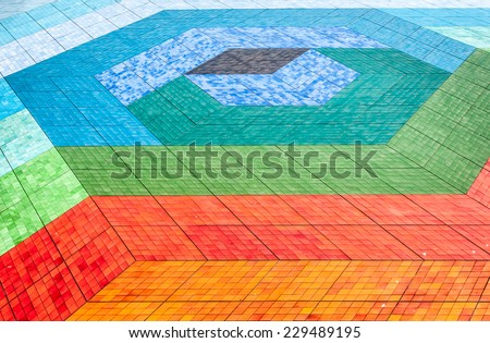 Tiled mosaic floor of different colours. Bright and colorful floor composition of tile in geometric style: square and diamond shape. Abstract background in tints of blue, green, orange and red. - stock photo