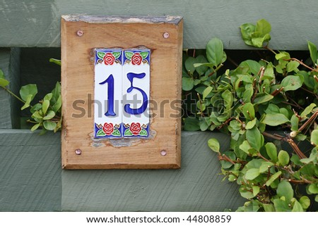tiled number fifteen sign for home against green fence with vegetation - stock photo