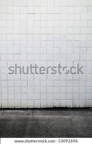 Tiled wall with a blank white bricks and gray spray painted graffiti. - stock photo