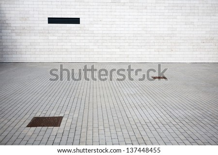 Tiled wall with a blank white bricks and paving - stock photo