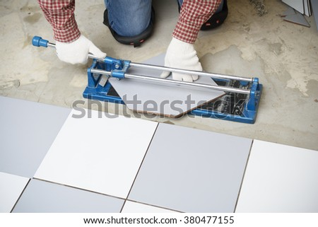 Tiler cutting ceramic tiles during floor installation - stock photo