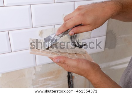 Tiler hands in the process of laying white rectangular tiles on the kitchen wall or bathroom wall Rectangular white ceramic tile with a chamfer on the kitchen wall.  Repair of apartments
