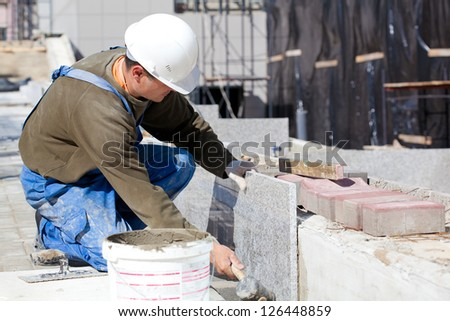 Tiler in helmet and work wear installing marble tiles at construction site - stock photo