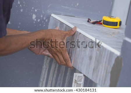 Tiler install ceramic tiles at construction site
