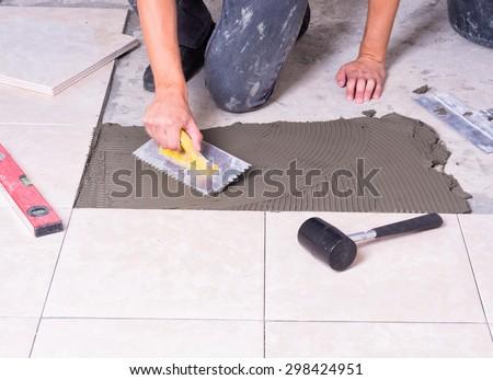 Tiler installing ceramic tiles on a floor - stock photo