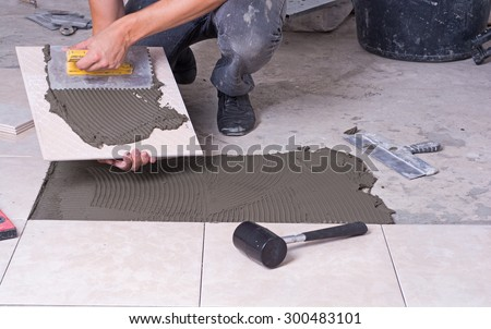 Tiler installing ceramic tiles on a floor - stock photo