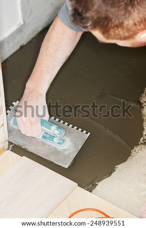 Tiler installs ceramic tiles at home.  - stock photo