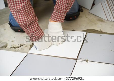 Tiler installs ceramic tiles on a floor - stock photo