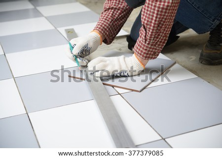 Tiler marks the tile during the floor installation - stock photo