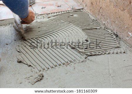 Tiler works with flooring in the backyard. - stock photo