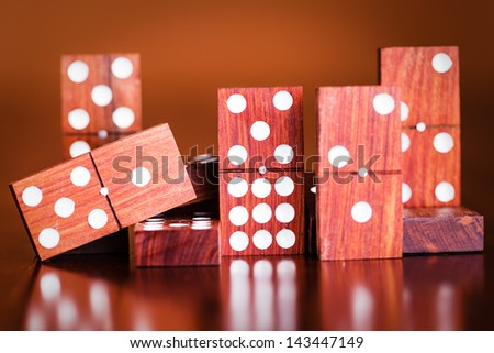 Tiles from a game of dominoes with reflections on a polished wooden table - stock photo
