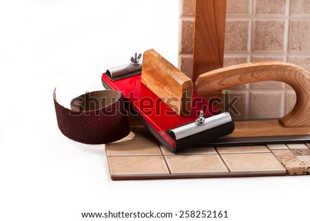 Tiles, tools for sanding walls, sandpaper, a square on a white background - stock photo