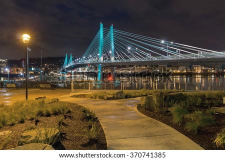 Tilikum Crossing Bridge Over Willamette River by the Waterfront Walkway in Portland Oregon at Night - stock photo