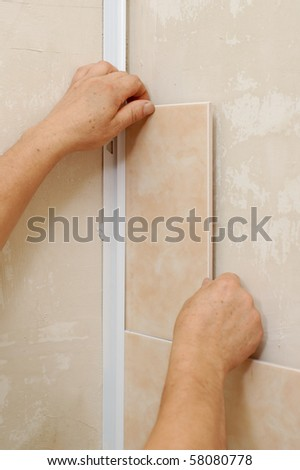 tiling - man installs ceramic tile - stock photo