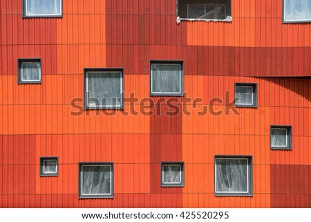 Tiling Tiles on the wall of a modern building. Orange color, waved.