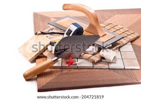 Tiling to floor and walls, a trowel, a meter on a white background - stock photo