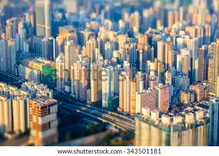 Tilt shift blur effect. Abstract futuristic cityscape with modern skyscrapers. Hong Kong aerial view evening panorama - stock photo