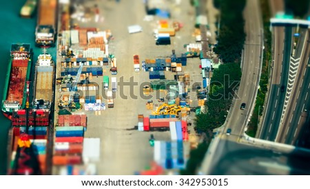 Tilt shift blur effect. Aerial view cargo ships loaded by crane with cargo containers at a busy port terminal. Hong Kong - stock photo
