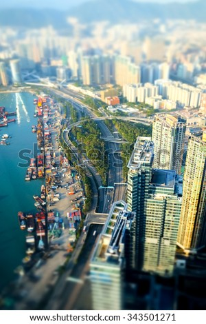 Tilt shift blur effect. Aerial view of Hong Kong Island with port terminal at Victoria Harbor. Abstract futuristic cityscape with skyscrapers