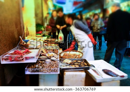 Tilt shift blur effect. People buy seafood on the traditional asian street market. Hong Kong city street life - stock photo