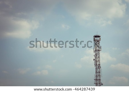 Tilt shift blur effect.telecommunications tower with blue sky clouds background
