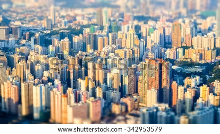 Tilt shift effect. Abstract futuristic cityscape with modern skyscrapers. Hong Kong aerial view evening panorama - stock photo