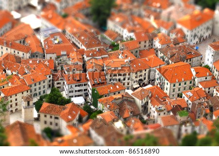 Tilt-shift miniature effect of bird eye view of buildings in Kotor old town, Montenegro - stock photo