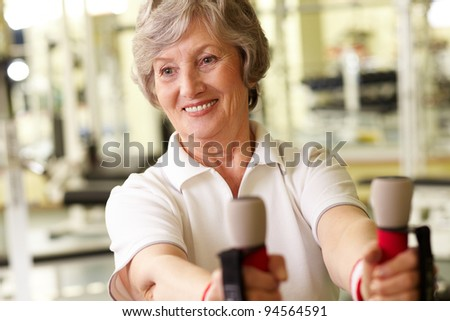 Tilt up of a pretty mature lady working out at gym - stock photo
