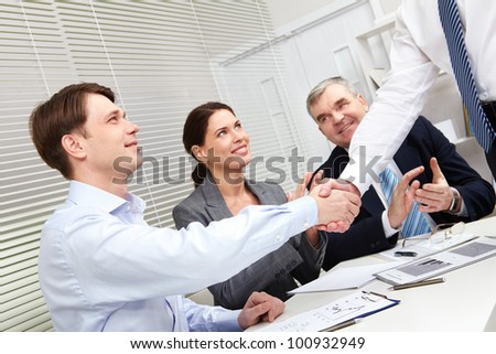 Tilt-up of business people giving a handshake to conclude the deal