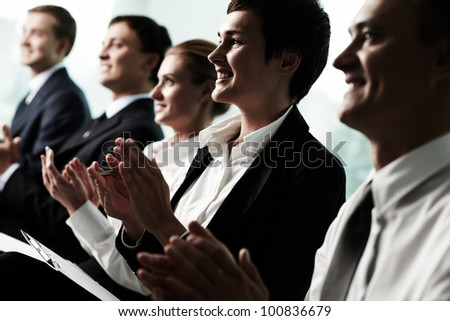 Tilt up of row of business people applauding to a successful speaker - stock photo