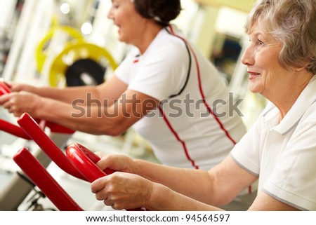 Tilt up of two active senior women doing fitness at gym - stock photo