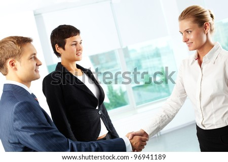 Tilt up shot of business people shaking hands looking positively - stock photo