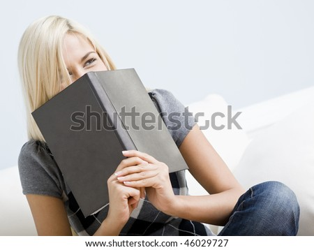 Tilt view close-up of woman sitting on white couch and giggling as she hold a book up to her face. Horizontal format. - stock photo