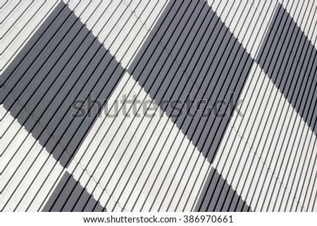 Tilt view of technological wall / partition surface consisting of profiled / corrugated metal sheets. Abstract black and white industrial background with square / rhombus pattern.