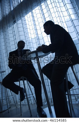 Tilt view silhouette of African-American and Asian businessmen sitting at a table and having coffee in front of a curtained window. Vertical format. - stock photo