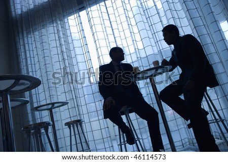 Tilt view silhouette of African-American and Asian businessmen sitting at a table having coffee in front of a curtained window.