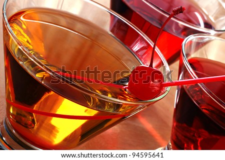 Tilted composition of cocktail drinks with backlighting and abstract reflections.  Macro with shallow dof.  Selective focus on the cherry. - stock photo