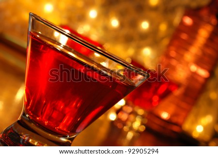 Tilted composition of red cocktail drink on bar with additional drinks, a bottle and defocused golden lights in background.  Macro with shallow dof. - stock photo