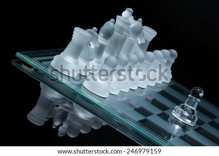 Tilted image of a lonely pawn against the entire set of opponent's pieces .   - stock photo