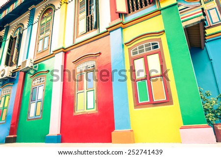 Tilted perspective of colorful houses facade of ancient traditional buildings in Little India - World famous multicolored district in Singapore - Soft desaturated vintage filtered look - stock photo