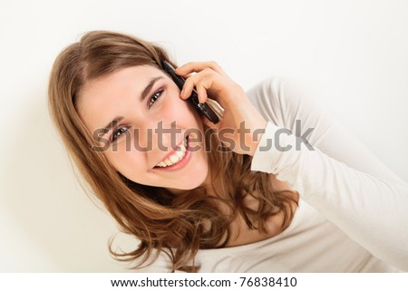 Tilted portrait of happy young woman talking on her cell phone