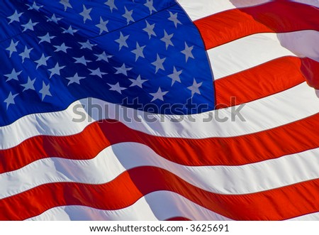 Tilted stars and stripes flying in the wind on nice background for a patriotic display - stock photo
