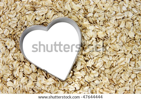 tilted white heart outlined with silver on a bed of oatmeal; white heart can be filled with text
