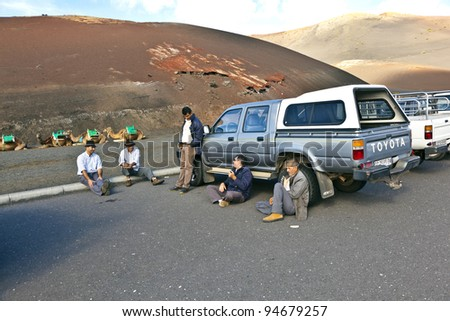 TIMANFAYA NATIONAL PARK, LANZAROTE, SPAIN - DECEMBER 26: Camel riders wait for tourists being guided by local people through the famous Timanfaya National Park in December 26, 2010 in Lanzarote, Spain - stock photo