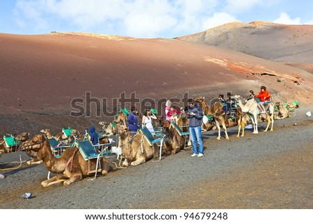 TIMANFAYA NATIONAL PARK, LANZAROTE, SPAIN - DECEMBER 26: Tourists riding on camels being guided by local people through the famous Timanfaya National Park in December 26, 2010 in Lanzarote, Spain - stock photo