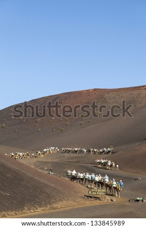 TIMANFAYA NATIONAL PARK, LANZAROTE, SPAIN - MARCH 28: Tourists ride on camels  guided by local people through the famous Timanfaya National Park on March 28, 2013 in Lanzarote, Spain. - stock photo